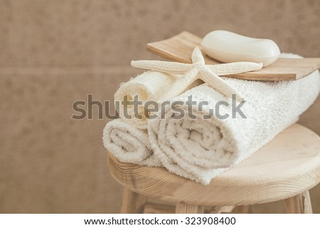 Hotel bathroom decor closeup. White towels, soap, loofah and starfish on wooden stool over stone tile. Natural colors, still life. - stock photo