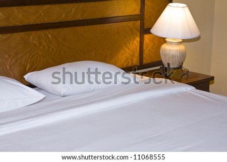 Hotel bed with lamp - stock photo