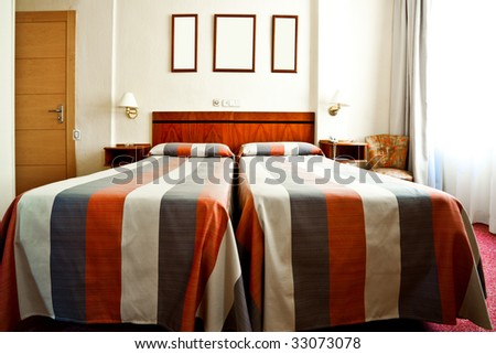 Hotel bedroom interior with bads, lamps and frames on the wall - stock photo