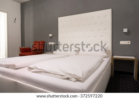 Hotel bedroom with a queen size bed - stock photo