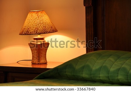 Hotel bedside with green bedspread - stock photo