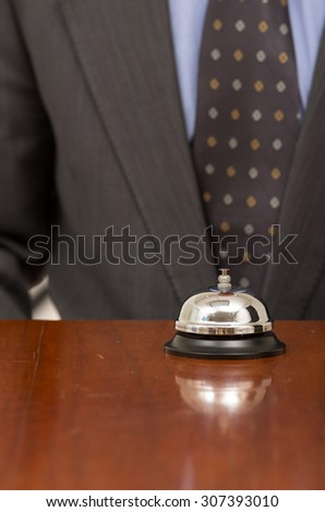 hotel bell in reception desk with man wearing suit in the background close up - stock photo
