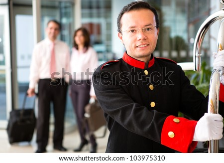 Hotel bellboy carrying the luggage of  a business couple