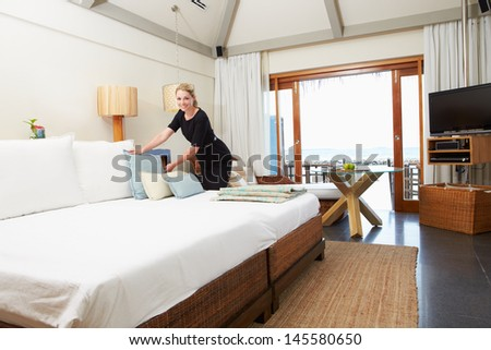 Hotel Chambermaid Making Guest Bed - stock photo