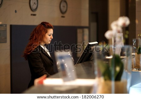 Hotel Concierge .Reception of hotel, desk clerk, woman taking a call and smiling.  - stock photo
