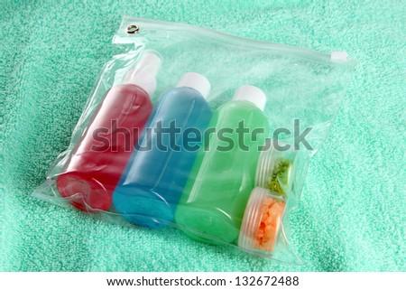 Hotel cosmetics kit on blue towel - stock photo