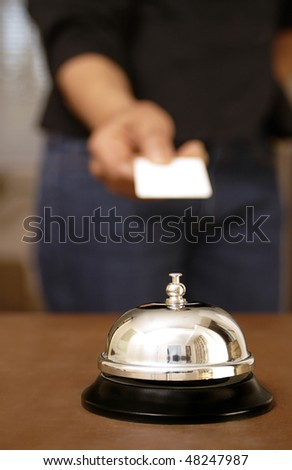 Hotel guest returning cardkey to concierge desk with bell in foreground