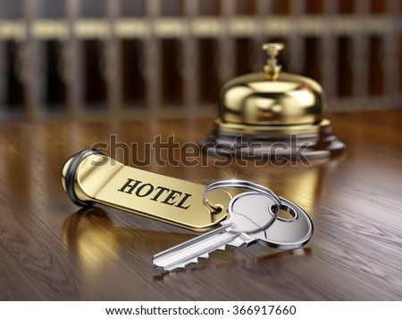 Hotel key and reception bell on reception desk - stock photo