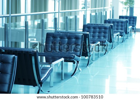 Hotel lobby in contemporary style. Black modern armchairs on glass floor. Selective focus