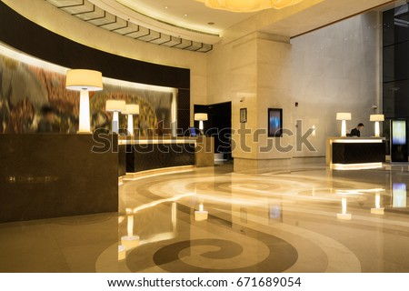 Hotel lobby interior with reception desk, marble floor and crystal lamp.