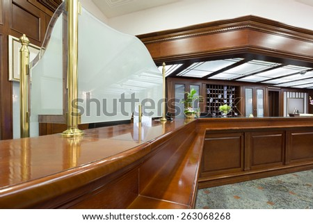 Hotel lobby with wooden reception desk - stock photo