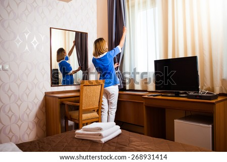 Hotel maid fixing the curtain - stock photo