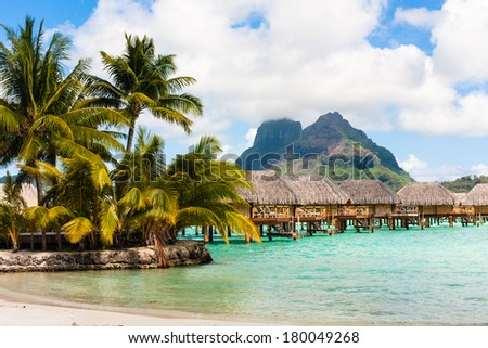 Hotel of the bungalows standing in water on a sandy beach - stock photo