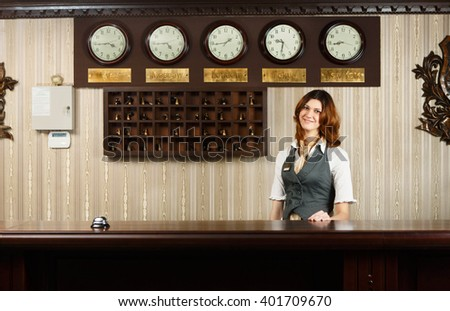 Hotel reception. Female receptionist at reception. Modern hotel reception counter desk with bell. Woman receptionist, concierge at desk. Travel, hospitality, hotel booking concept.  - stock photo