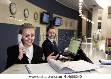 Hotel receptionist. Modern luxury hotel reception counter desk with bell. Two happy females receptionist worker standing at hotel counter. - stock photo