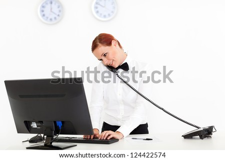hotel receptionist talking on phone while checking on computer - stock photo