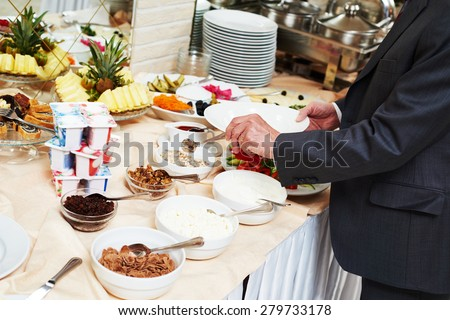 Hotel restaurant catering service. Man with food at morning buffet style smorgasbord breakfast - stock photo
