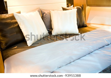 Hotel room bed with many pillows. - stock photo