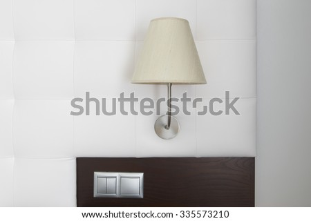 Hotel room interior detail with lamp, switches and white wall. Horizontal - stock photo