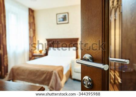 Hotel room or apartment doorway with open door and bedroom in background - stock photo