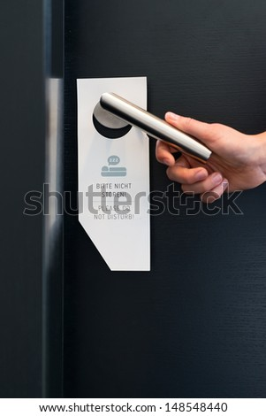 Hotel room service - someone ignores the please do not disturb sign on handle on door of suite in hotel - stock photo