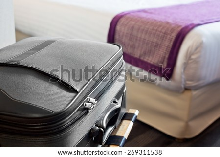 Hotel room with a suitcase on the luggage place and the bed - stock photo