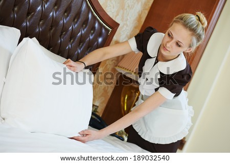 Hotel service. female housekeeping worker maid making bed with bedclothes at inn room - stock photo