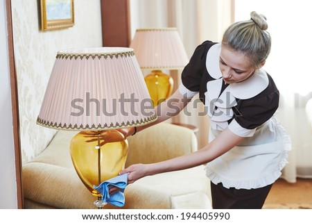 Hotel service. female housekeeping worker with cleaning table from dust in room - stock photo
