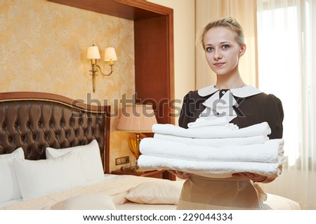 Hotel service. female housekeeping worker with towels and bedclothes at inn room - stock photo