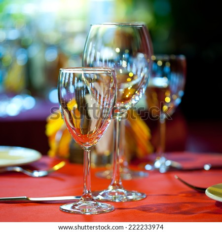 Hotel service: table in a restaurant with a red tablecloth, red napkins, wine glasses and cutlery. - stock photo