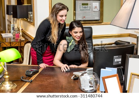 Hotel staff at work, reception shot. - stock photo