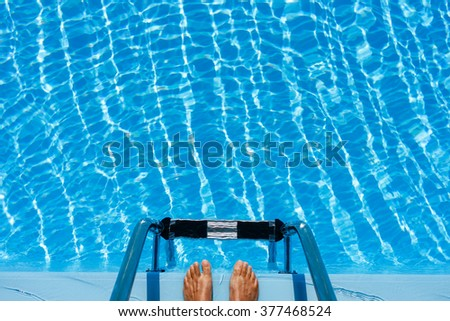 Hotel swimming pool with blue and sunny reflections, in a hot summer vacations. - stock photo