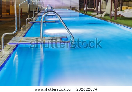 Hotel swimming pool with night lighting fittings under water .