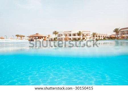 Hotel swimmung pool.Low angle view from the water - stock photo