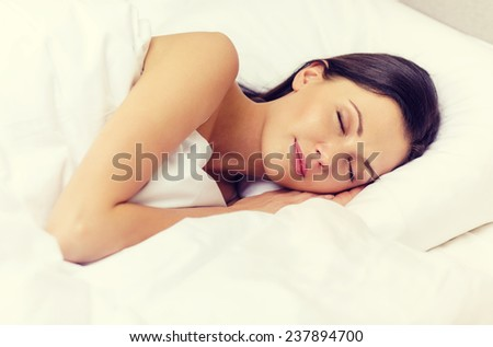 hotel, travel and happiness concept - beautiful woman sleeping in bed - stock photo