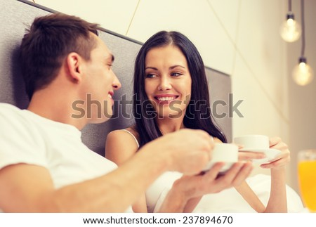 hotel, travel, relationships and happiness concept - smiling couple having breakfast in bed in hotel room - stock photo