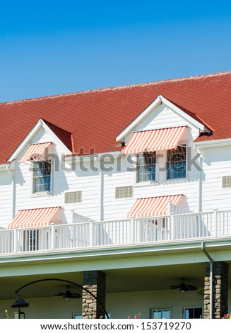 Hotel with red roof and red and white awnings