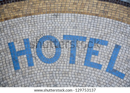 Hotel written in mosaic in front of the entrance - Paris, France.