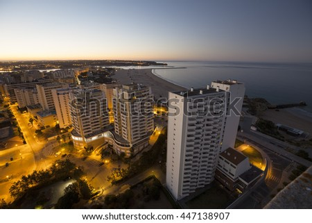 Hotels and beach at the bank of the ocean during sunrise. View from above. Pria Da Rocha, Portimao, Portugal.