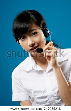Hotline, closeup portrait of Asian business woman on studio blue background.