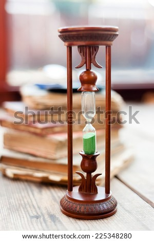 Hour glass and old books on wood background