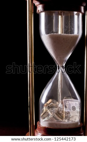 hour glass on a dark background with american money in it