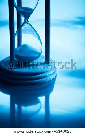 hour-glass with reflection in blue light - stock photo