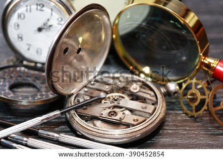 Hour workshop. Vintage still life with ancient silver pocket watch - stock photo