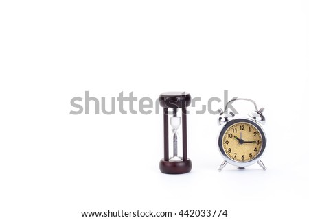 Hourglass and alarm clock  on a white background The concept of waiting hopefully. - stock photo