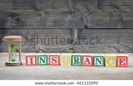 Hourglass and word insurance on wooden table