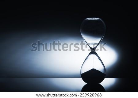 Hourglass clock on dark background - stock photo