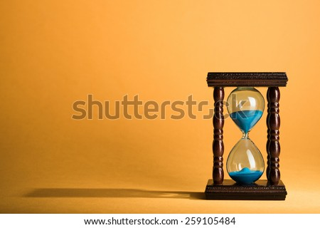 Hourglass clock on yellow vintage background - stock photo
