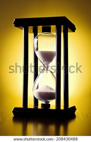 Hourglass counting down the time with sand running through the glass bulbs, close up view on a yellow background - stock photo