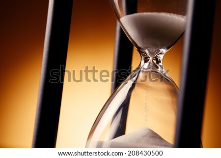 Hourglass counting down the time with sand running through the glass bulbs, close up view on a golden background - stock photo